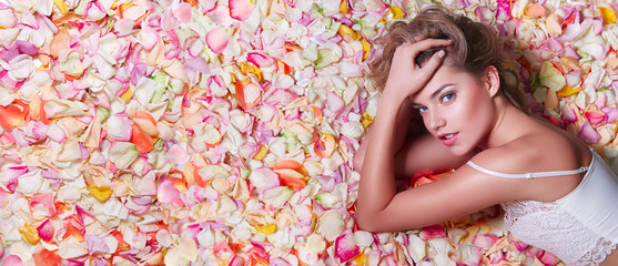 Valentine's Day. Loving girl. The girl in white dress lying on the floor in the petals of roses. Background of white, orange, red, pink rose petals. Pink lipstick on the lips from the beautiful girl.