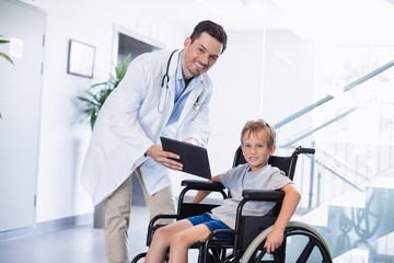 Doctor showing digital tablet to  disable boy