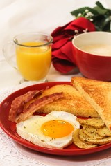 Valentine breakfast with heart shaped egg bacon bread toast cup of coffee served in red plate