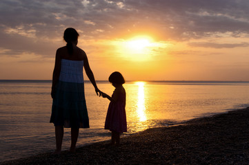 Mother and kid silhouettes on sunset beach, family summer vacation