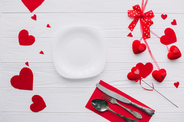 valentines day.plate ,cutlery ,knife,fork,red hearts on white wooden background