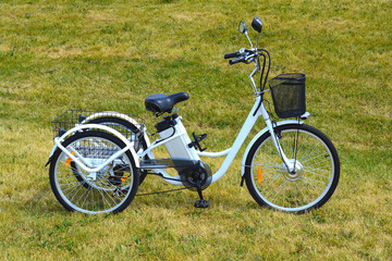 Electric trike or bicycle in the park in sunny summer day. Shot from the side. Unfiltered, with natural lighting. The view of the e motor and power battery of the three wheel bike.