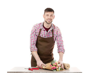 Male florist wrapping flower bouquet in paper on white background