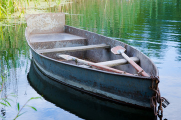 Old metal row boat on small lake