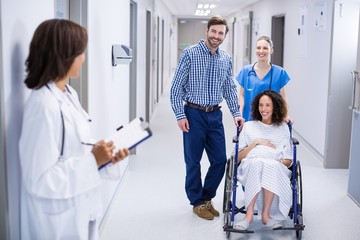 Doctor interacting with pregnant woman in corridor