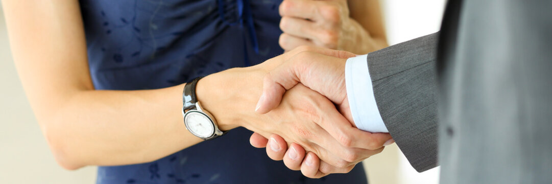 Businessman and woman shake hands as hello in office closeup