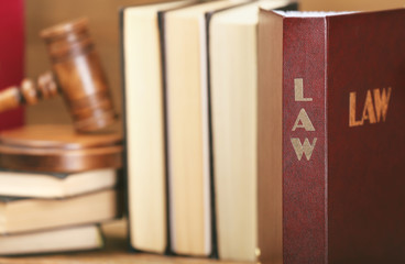 Law book with judge gavel on background