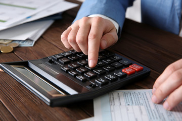Man sitting at table with calculator