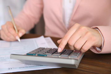 Woman sitting at table with calculator, document and pen