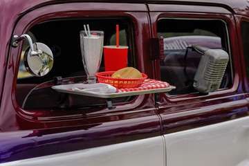 Drive in movie theater speaker and food tray on vehicle