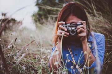 Happy young hipster woman with vintage camera in field.