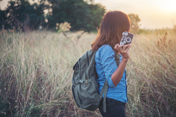 Young hipster woman backpacker with vintage camera.