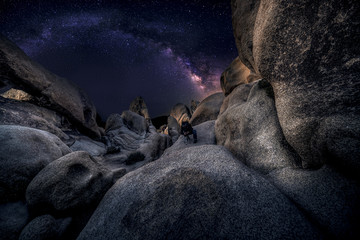 Obraz Photographer doing astro photography in a desert nightscape with milky way galaxy.  The background is stary celestial bodies in astronomy.  The heaven depicts science and the divine. - fototapety do salonu