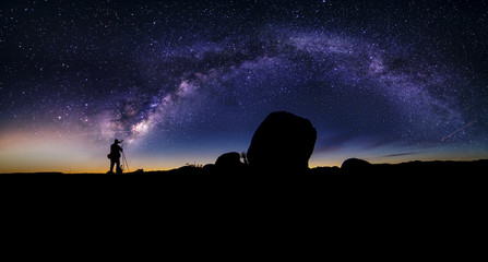 Photographer doing astro photography in a desert nightscape with milky way galaxy.  The background is stary celestial bodies in astronomy.  The heaven depicts science and the divine.