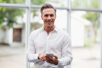 Happy businessman holding mobile phone
