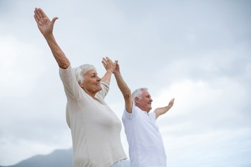 Senior couple standing with arms outstretched on the beach