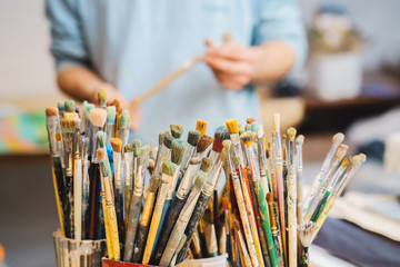 Paint Brushes on a blur background and artist is holding the brush