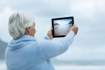 Senior woman photographing scenery using digital tablet