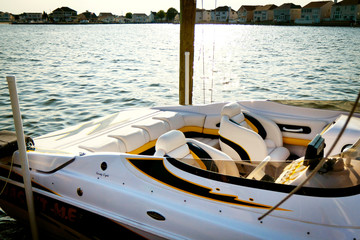 Small white speed boat docked with leather seat