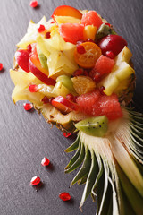 Ripe pineapple stuffed with fresh tropical fruits close-up. vertical
