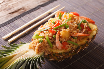 Thai pineapple stuffed with rice, shrimp, chicken and vegetables close-up. horizontal
