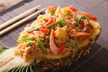 Pineapple stuffed with fried rice, shrimp and vegetables close-up. Horizontal