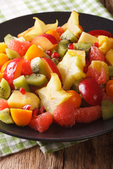 Salad of fresh tropical fruits close-up on a plate. vertical