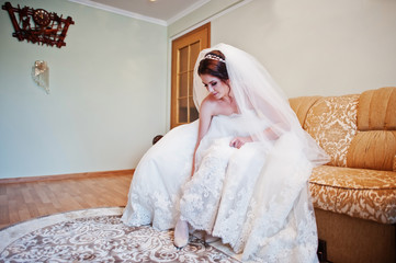Brunette bride sitting on bed and wear her wedding shoes.