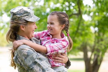 Happy female soldier with her daughter in park