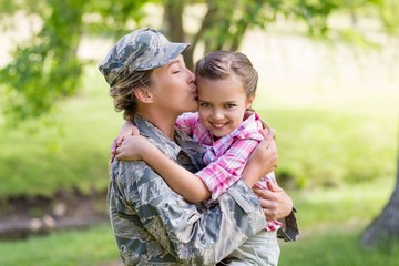 Happy female soldier kissing her daughter in park
