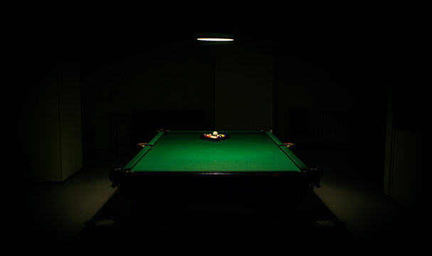 snooker in the dark. billiards in the center under lamp light in the darkness. pills balls and lamp. empty billiard room