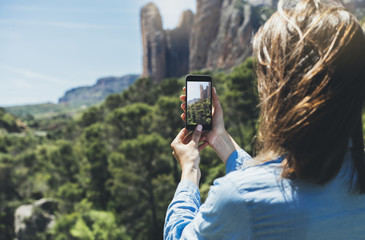Hipster girl making photo on smartphone mobile closeup, view tourist hands using gadget phone in travel on background mountains and sky landscape; finger touch screen cellphone mockup