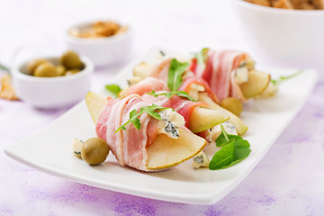 Appetizer with pear, blue cheese, prosciutto ham and toast for holidays on a white plate.