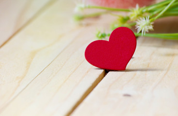 Closeup heart on the wood table with flower background,Valentine's day.