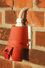 Rote Außen- Steckdose an einer Ziegelmauer