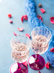 Two stemmed champagne glasses on blue textured background with pink dried flowers. Valentine's day wedding romantic date invitation