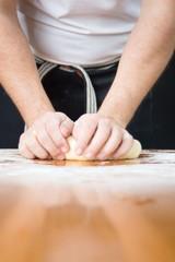 Man kneading dough on flour covered table
