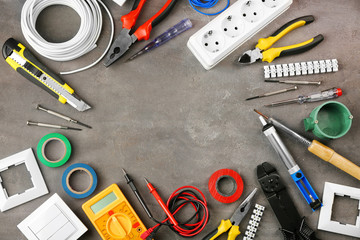Different electrical tools on grey background