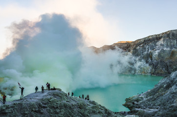 Posing for photos at sunrise with the smoking sulphuric cloud of mount Ijen behind