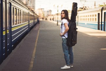 Woman with guitar at the railway station