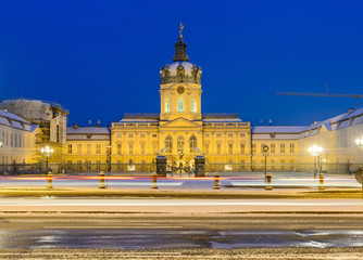 Snowy road and Charlottenburg Palace in background in a winter night, Berlin, Germany, Europe