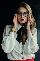 Indoor waist up portrait of young beautiful fashionable business woman posing on dark background. Model looking at camera. Lady wearing stylish eyeglasses, golden wrist watch. Female fashion concept
