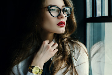 Indoor close up portrait of beautiful fashionable business woman posing in loft interior. Model looking through window. Lady wearing eyeglasses, wrist watch. Female fashion concept. Dark background
