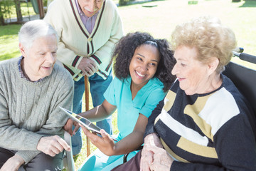 African nurse helping elderly people using tablet outdoor