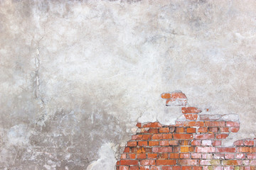 brick wall with damaged plaster, background shattered cement sur