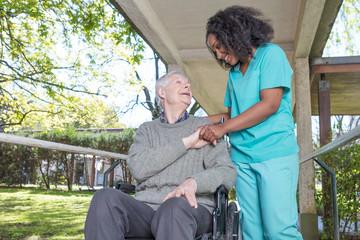 African nurse assisting elderly man on wheelchair outdoor