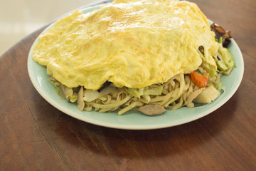 Myanmar food fried noodle cover omelet on  wooden table