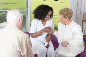 African nurse handing glass of water to elderly woman in hospita