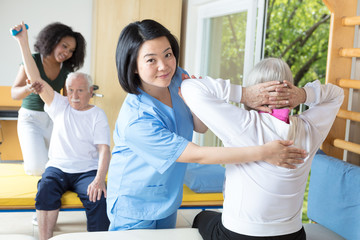 Rehab clinic gym. Elderly man and woman assisted by nurses