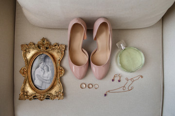 Wedding accessories: photo frame with bride and groom portrait, bridal shoes, perfume bottle, jewelry and wedding and engagement rings